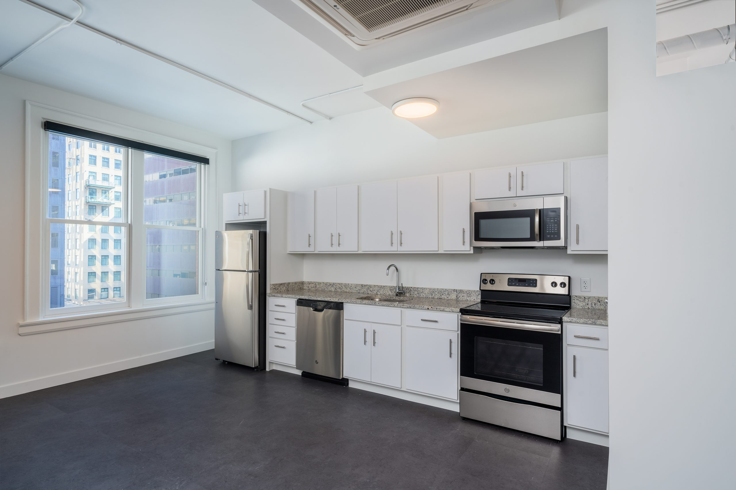 Modern sleek kitchen in studio apartment in the Edna Griffin building with stainless steel appliances and white cabinets