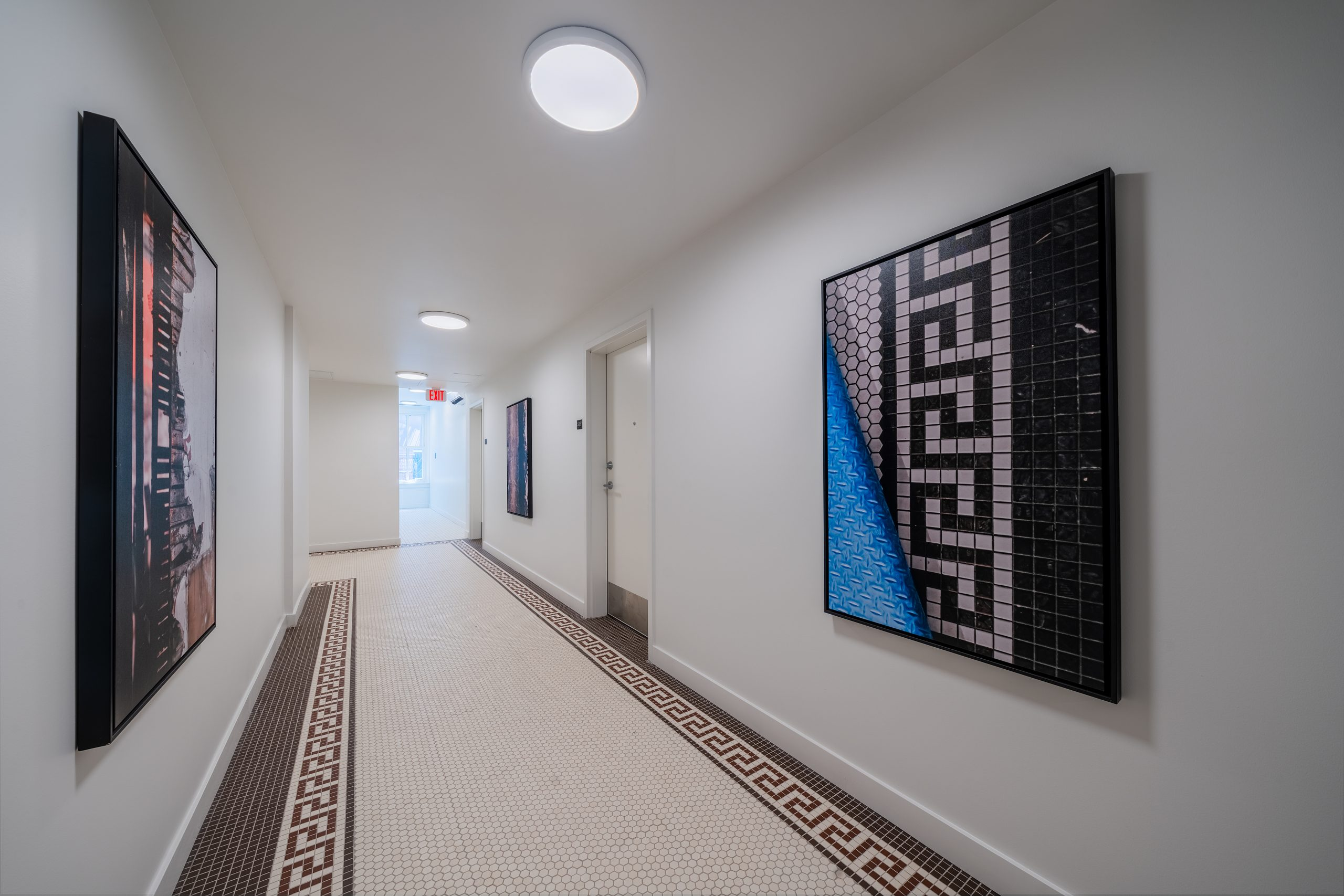 Interior hallway in the Edna Griffin building displaying restored original tile in a Greek pattern with matching artwork on the wall