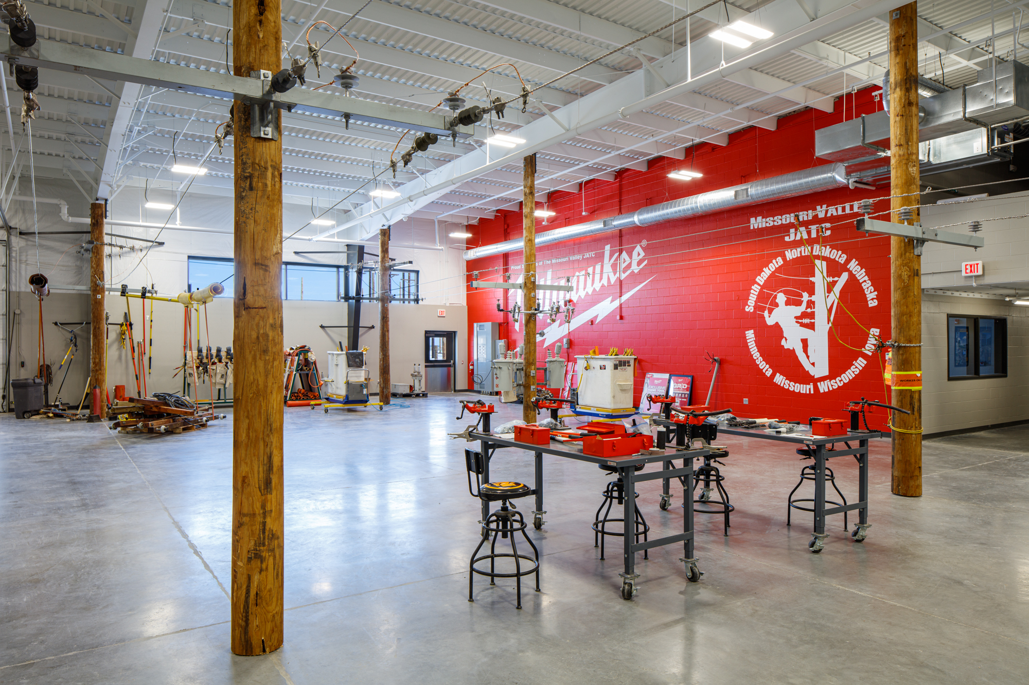 Interior of Missouri Valley JATC showing the maintenance shop with a red feature wall that has a white MVJATC logo. Work tables, open space, and lots of tools.