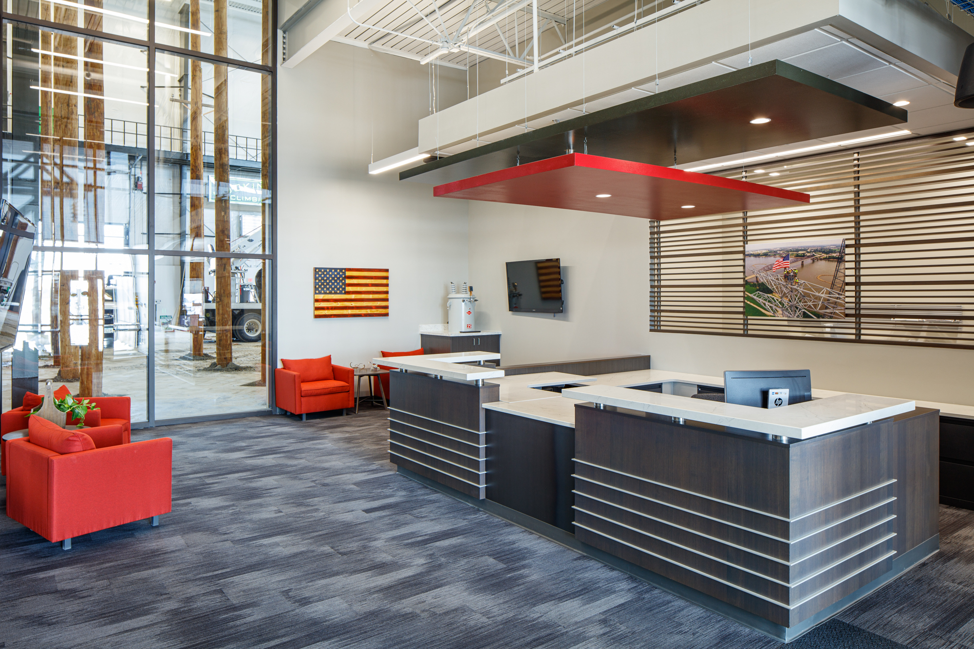 Interior grey carpet with red furniture (individual chairs) and red hanging light feature. Handcrafted slate grey desk with white walls and floor to ceiling window viewing into the interior pole yard.