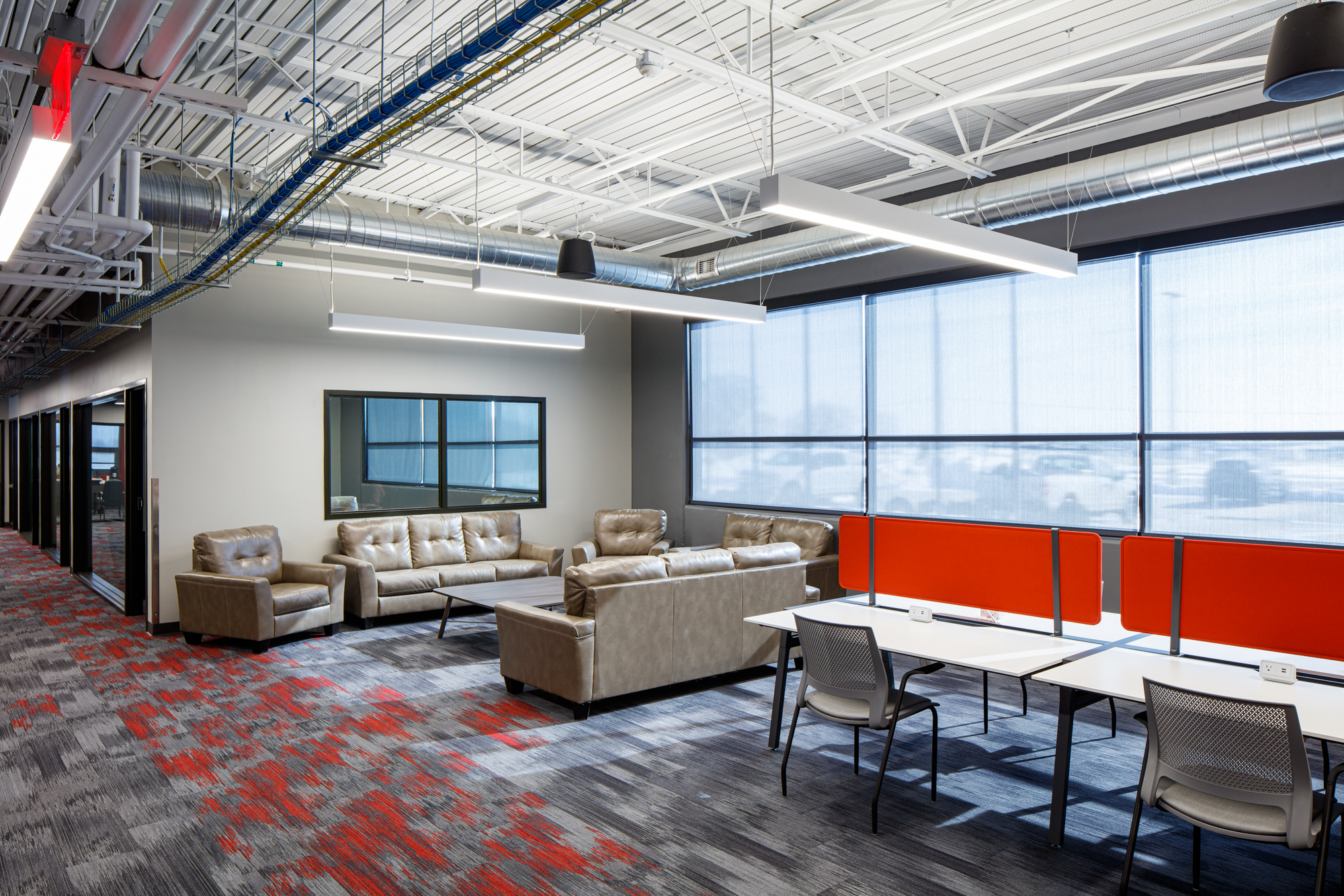 First floor grey and red carpeting showcasing beige couches and open desk workspaces divided by adjustable red walls with large windows facing the front parking lot