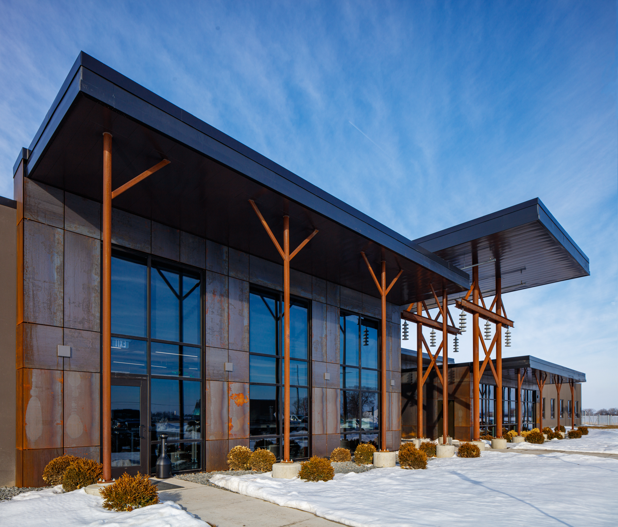Large windows with medical walls and natural wood poles for the front exterior of the MVJATC building during winter with light snow on the ground